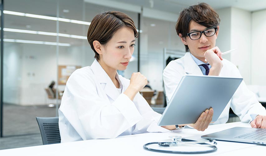 two scientists looking at a tablet